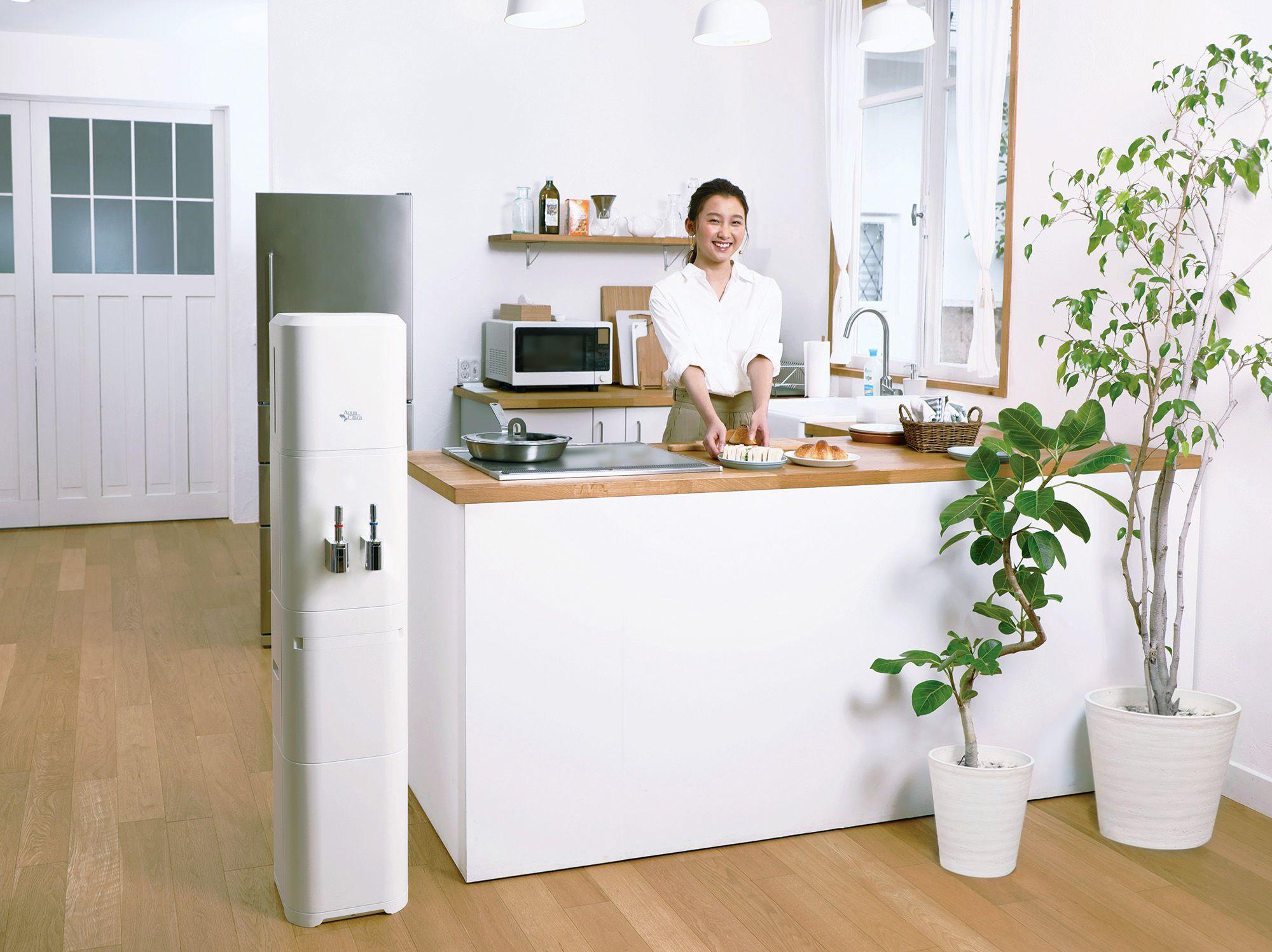 カウンターキッチンで食事の用意をしている女性とキッチン横にアクアクララ AQUA FABが設置されている写真